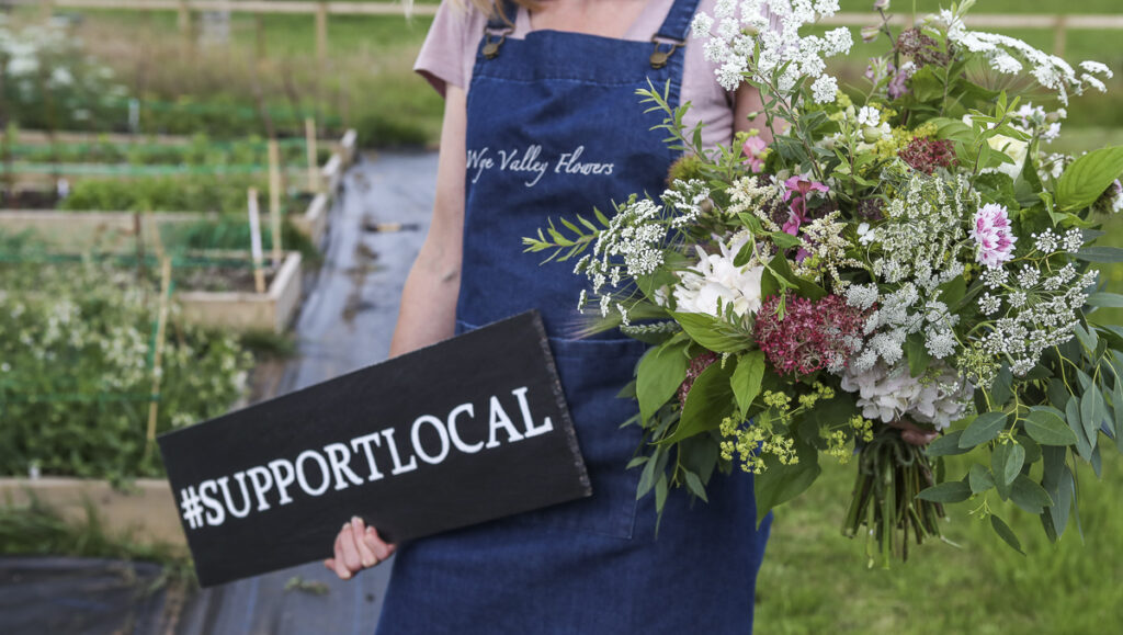 Lucy of Wye Valley Flowers holds a sign showing their support for local business