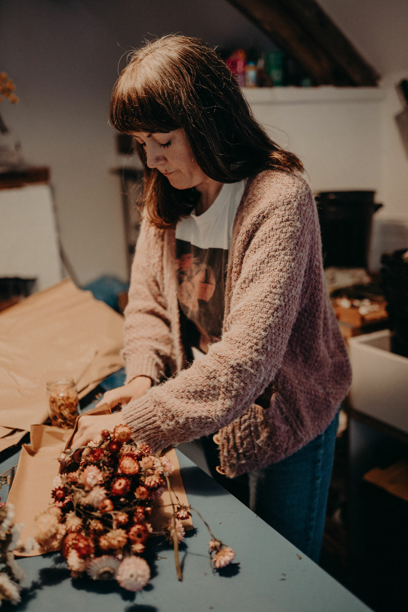 Lucy Marshall of Deadhead Flower Farm wrapping bunches of dried flowers grown and dried at her farm