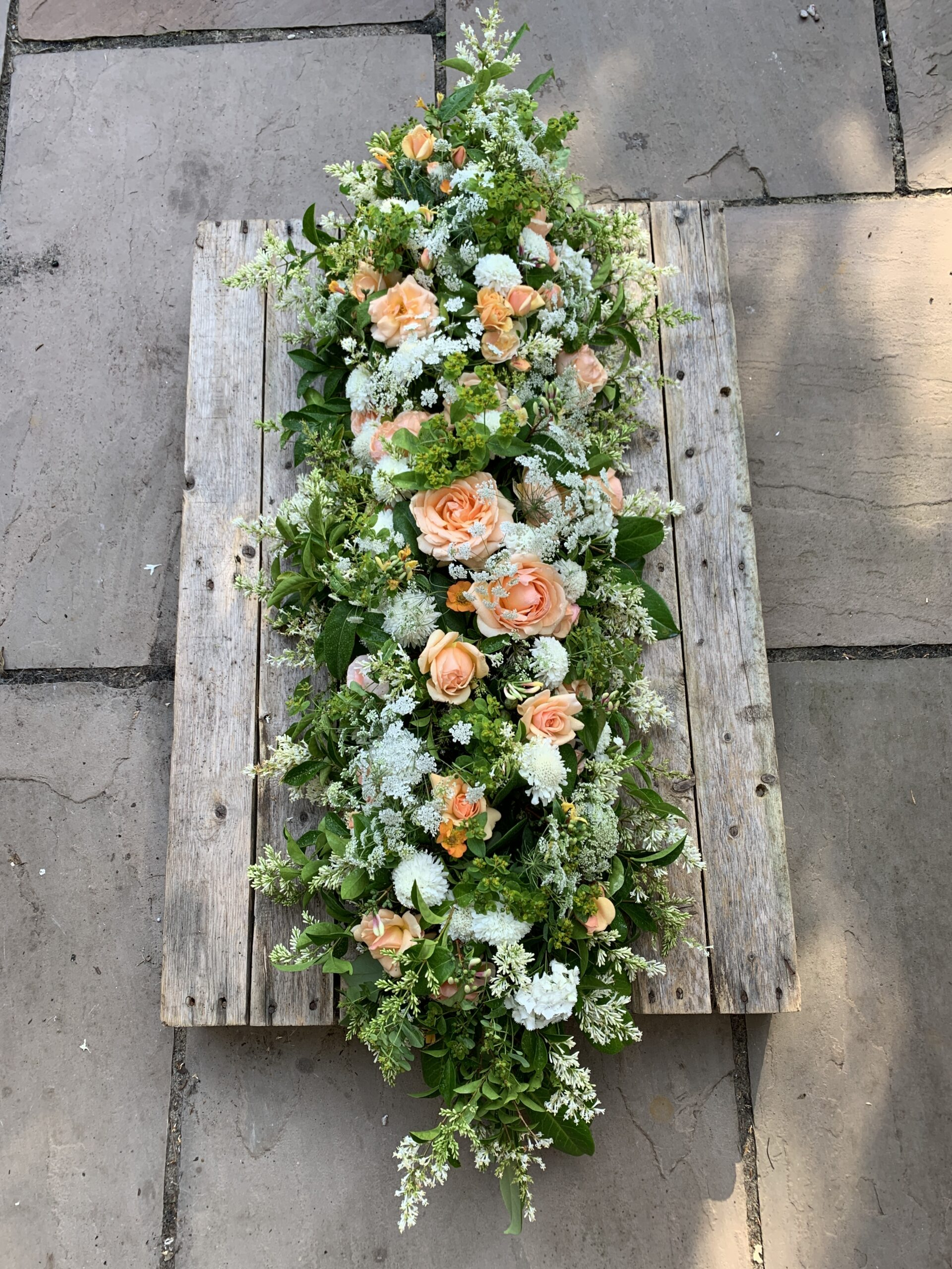 A seasonal casket arrangement of British flowers designed by The Posy Patch