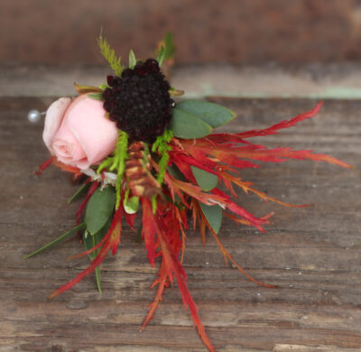 An autumn groom's buttonhole with fiery autumn leaves and the last of the roses. Tuckshop Flowers Birmingham