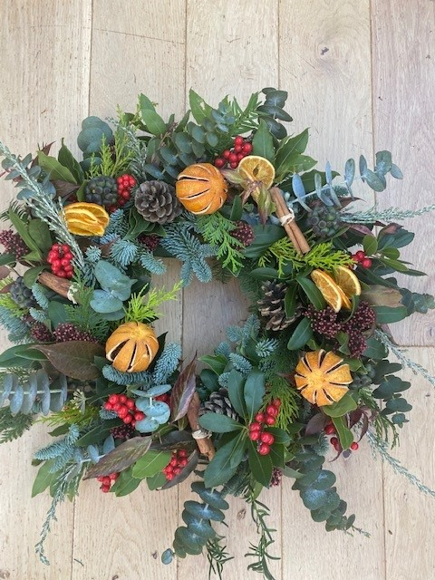 A traditional fresh evergreen wreath with spruce, eucalyptus and dried oranges.