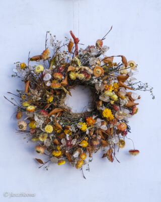 A wreath with sustainable flowers at its heart. Locally grown dried strawflowers adorn a sustainable, biodegradable base. By Fierceblooms, Cheshire.