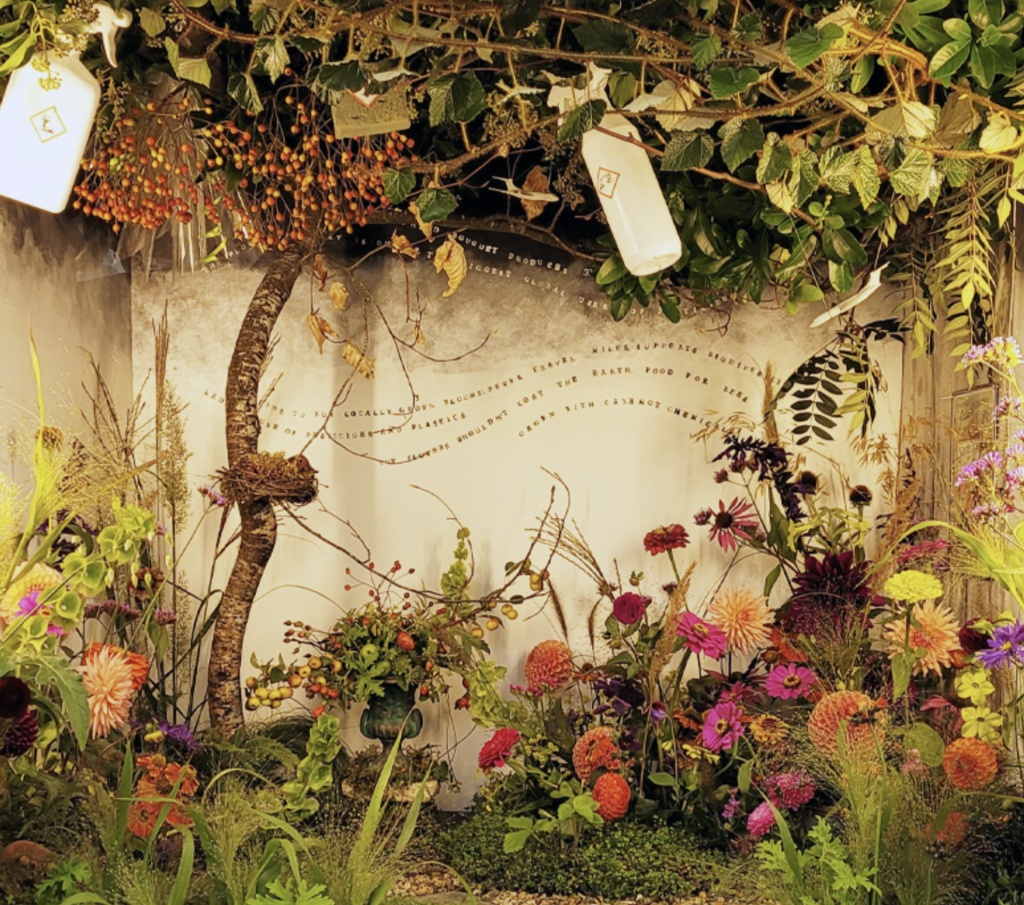 An imaginative autumn display by the Fairford Flower Collective featuring dahlias, crab apples, grasses and messages about the sustainability of the floristry industry